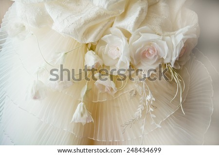 Pleated silk champagne color with artificial flowers. Detail of wedding dress - stock photo