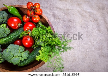 Plenty of colorful vegetables in wooden plate on linen background with copy space - stock photo