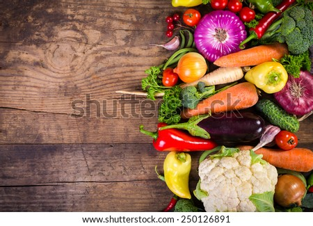 Plenty of colorful vegetables on wooden table with copy space - stock photo