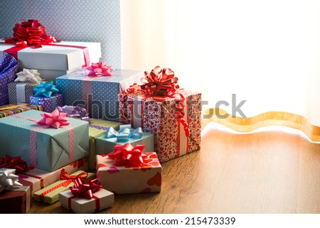 Plenty of colorful wrapped christmas presents on the floor next to the window. - stock photo