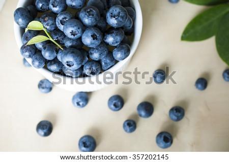 Plenty of fresh Blue berries on wooden table - stock photo