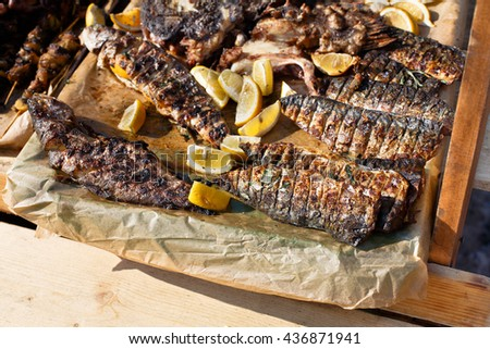 Plenty of seafood, mackerel fish grilled at barbecue. Mackerel and other seafood bbq outdoors at picnic, party. Street food, seafood takeaway at big tray. Grill crispy roasted fish with lemon - stock photo