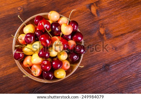 Plenty of sweet fresh cherry in the dish on wooden background - stock photo