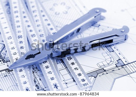 Pliers,  metric folding ruler and architectural plan of the modern house