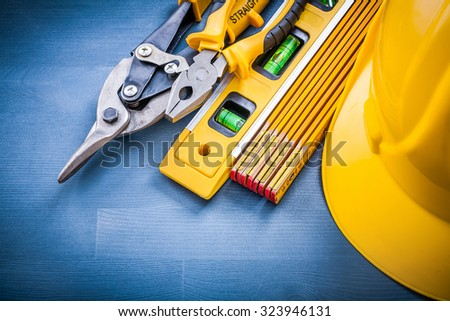 Pliers steel cutter hard hat wooden meter construction level.