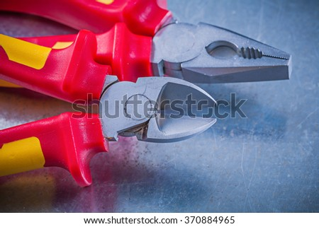 Pliers wire cutter on metallic background horizontal image electricity concept. - stock photo