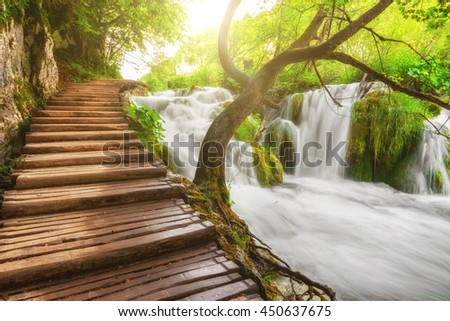 Plitvice Lakes National Park, tourist route on the wooden flooring along the waterfall, Croatia, nature sunny background - stock photo