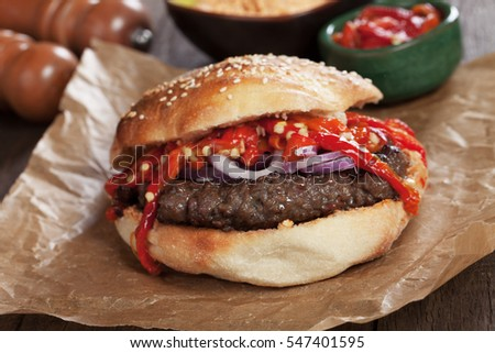 Pljeskavica, serbian style burger sandwich topped with roasted red peppers