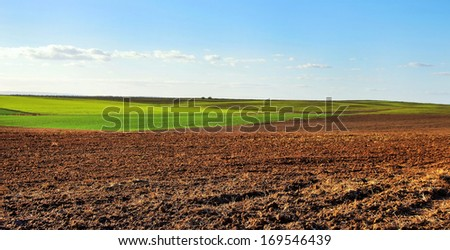 ploughed field under  cloudy sky, at sunset - stock photo
