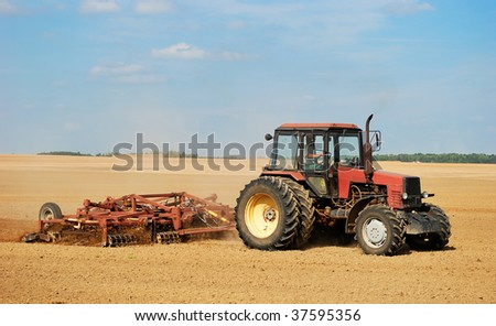 Ploughing tractor in yellow field outdoors in summer with plough - stock photo