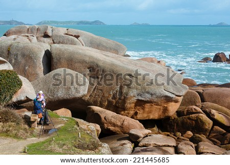 Ploumanach coast spring view and family on stony bench (Perros-Guirec, Brittany, France). The Pink Granite Coast. - stock photo
