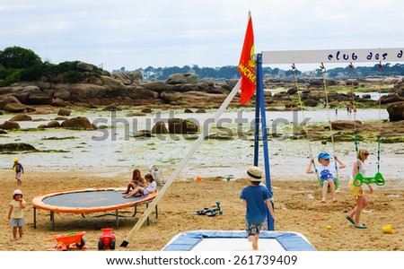 PLOUMANACH, FRANCE - JULY 16, 2014: Unidentified kids play in playground at Pink Granite Coast. Coast between Perros-Guirec and Ploumanach is one of the most popular Breton resorts for family vacation - stock photo