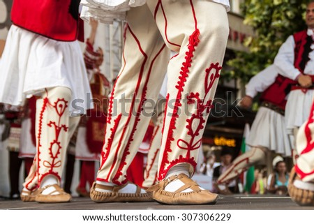 PLOVDIV, BULGARIA - AUGUST 06, 2015 - 21-st folklore festival in Plovdiv, Bulgaria. The folklore group from Bulgaria dressed in traditional clothing is preforming Bulgarian national dances. - stock photo