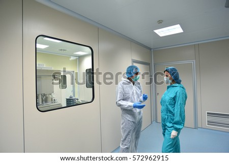 Plovdiv,Bulgaria - January 16, 2017 :  Operators with protective clothing inspecting a pharmaceutical plant