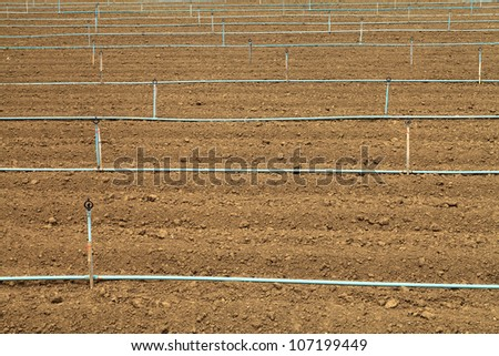 Plow land and irrigation system ready for agricultural - stock photo