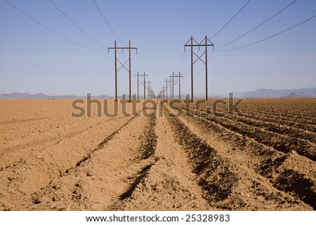 Plowed farm field with two high-tension power lines and desert mountains in the background. - stock photo