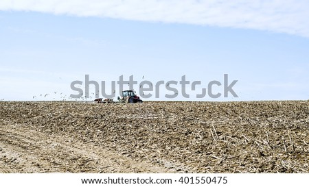 plowed field, a field for planting crops, tractor plowing a field, the beginning of the gardening season, spring - stock photo
