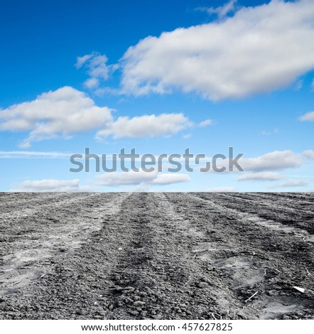 plowed field against the sky - stock photo