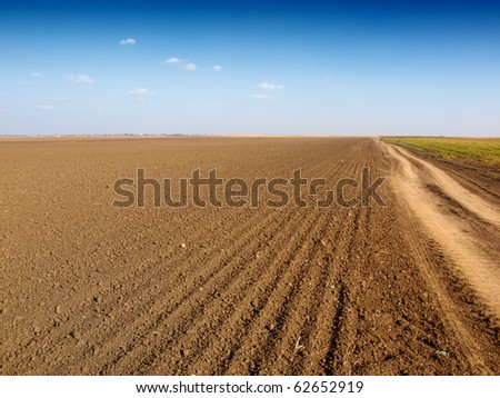 plowed field and dirt road - stock photo