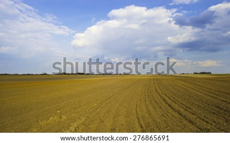 plowed field and the blue sky - stock photo