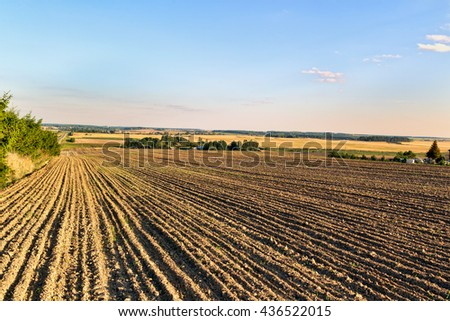Plowed field in autumn day - stock photo