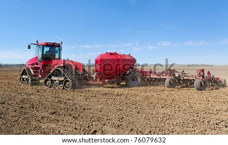 Plowed field with red tractor.