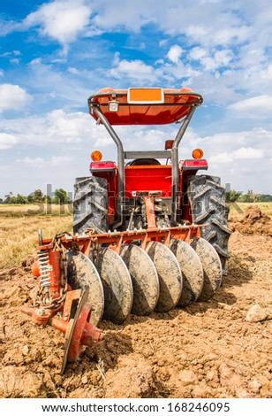 Plowing tracktor in the rice farm . - stock photo