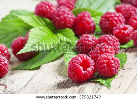 Plucked from the bush fresh garden raspberries with green leaves on the old wooden table in rustic style, selective focus - stock photo
