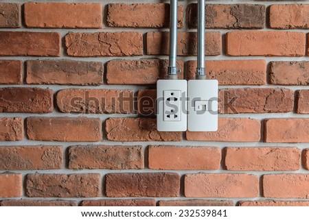 plug and telephone line on brick wall - stock photo