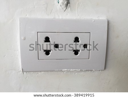 plug socket on white wall - stock photo