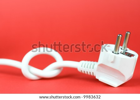 Plug tied in a knot on red background