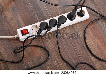 Plugged in electric devices in an extension cord - stock photo