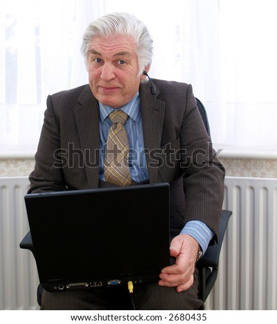 Plugged in to his laptop senior male - stock photo