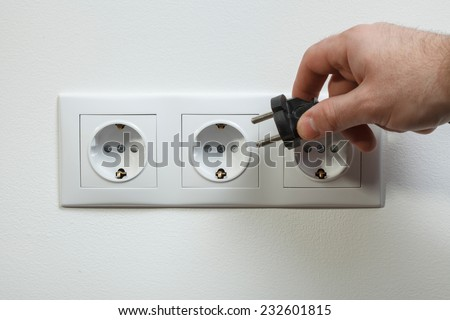Plugging black electrical cable to white socket - stock photo