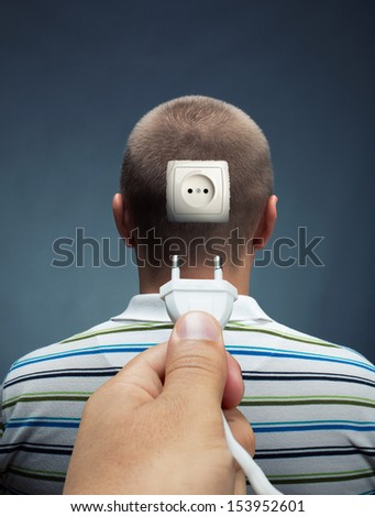 Plugging electrical cable into the outlet in head - stock photo