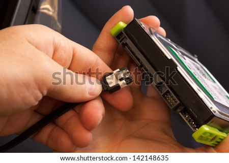 Plugging wire in to the hard disk drive - stock photo