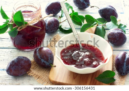 Plum jam and fresh plums over white wood background - stock photo