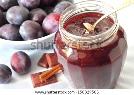 Plum jam with chocolate and cinnamon in a jar - stock photo