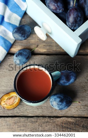 Plum Juice in a mug with fresh fruits - stock photo