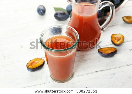 Plum Juice in jar and glass with fresh fruits - stock photo