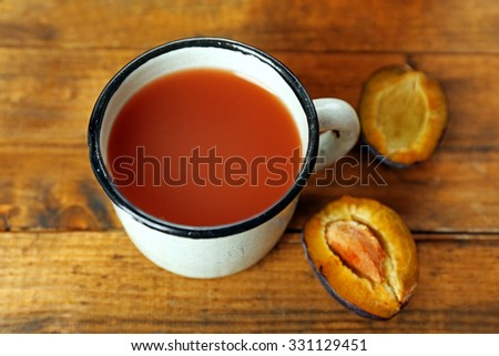Plum Juice in mug with fresh fruits