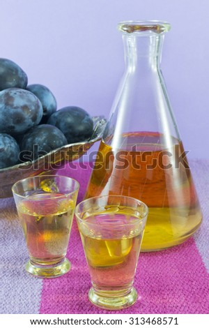 Plum schnapps and fresh plums served on the tablecloth