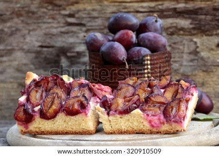 plum still life, cake, plums on wood - stock photo