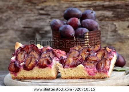 plum still life, cake, plums on wood - stock photo