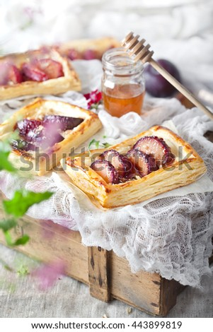 Plum tarts with honey, closeup top view shot, selective focus. Country style, light photo. Summer baking concept. - stock photo