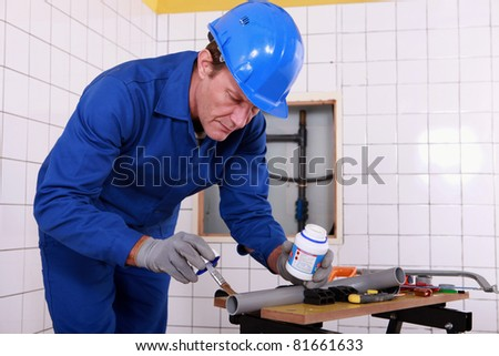 Plumber applying glue to a grey plastic pipe - stock photo