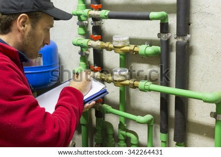 plumber at work making the consumption metering - stock photo