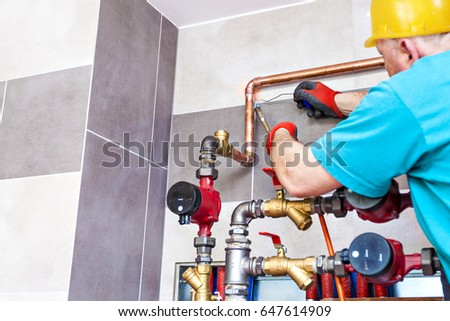 Plumber brazed copper tubes. Plumber assembles the central heating system in Boiler