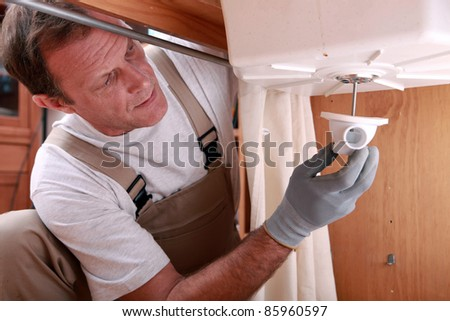 Plumber fitting a kitchen sink - stock photo