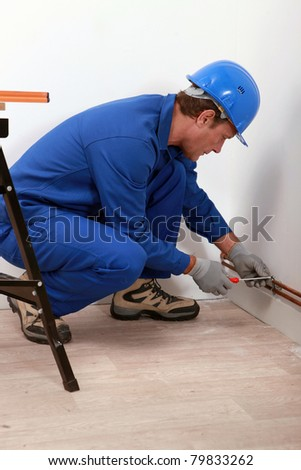 Plumber fitting copper pipe - stock photo